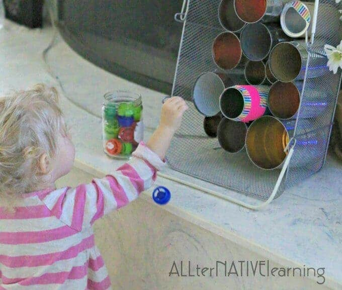 Toddler playing a tin can diy darts variation game | ALLterNATIVElearning