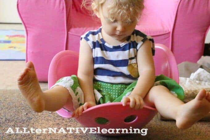 Toddler Playing with bilibo seat for gross motor skills, movement, and fitness | ALLterNATIVElearning