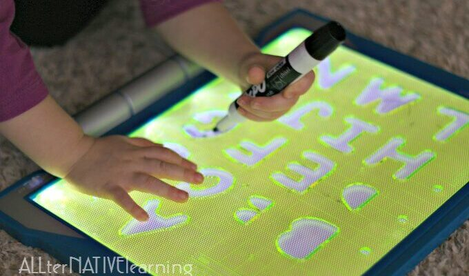Toddler learning letters with the light table and stencils | ALLterNATIVElearning