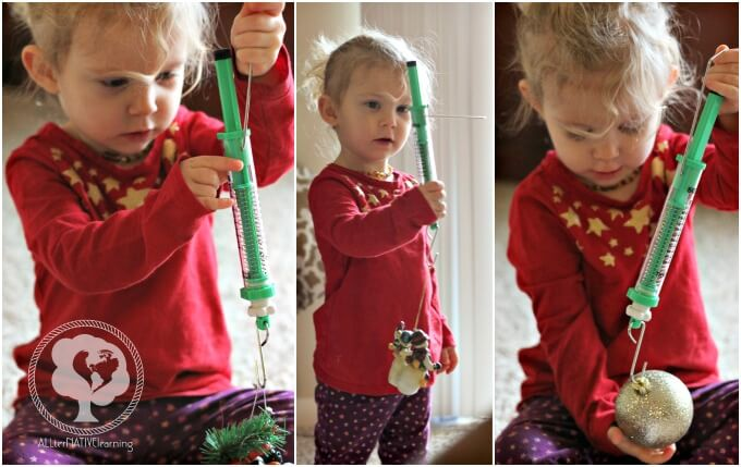 Toddler exploring measurement with ornaments and spring scales