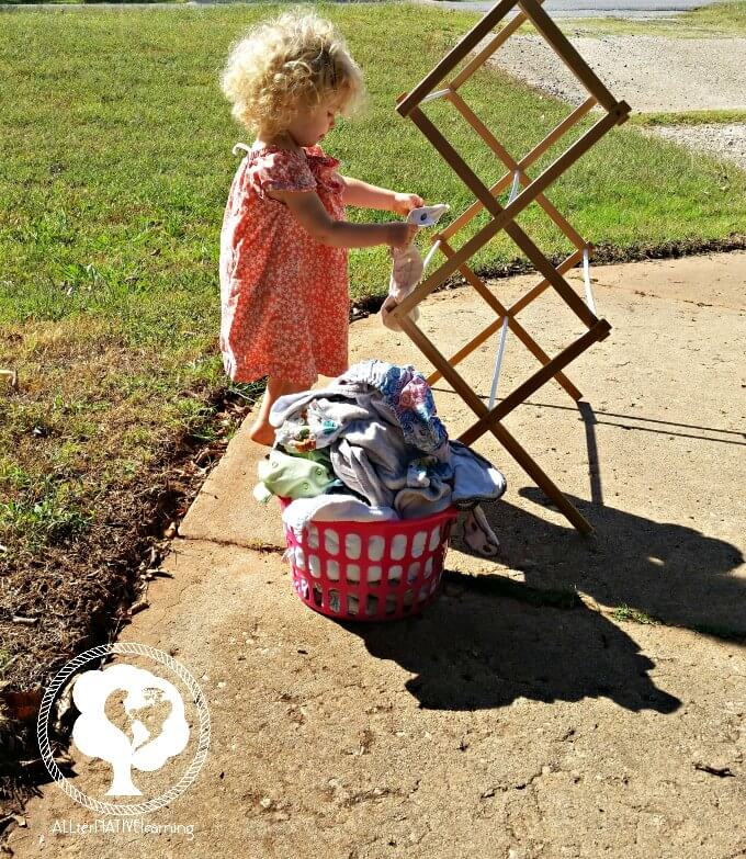toddler helping with hanging laundry