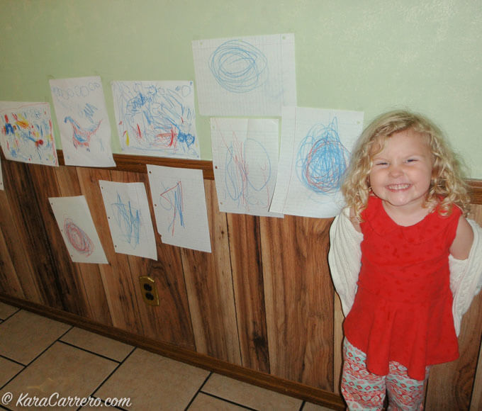 My granddaughter standing next to her drawings that inspired an art wall